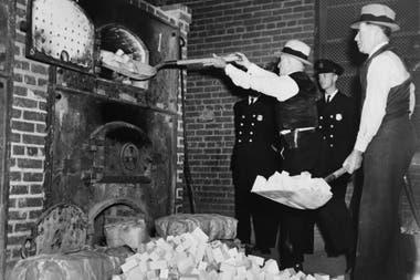 Agentes de la Oficina Federal de Estupefacientes de Estados Unidos introducen en una incineradora bloques de heroína confiscados en 1936