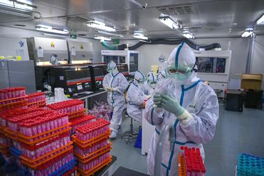 Esta foto tomada el 23 de noviembre de 2020 muestra a técnicos procesando pruebas de coronavirus Covid-19 en un laboratorio en Tianjin, China