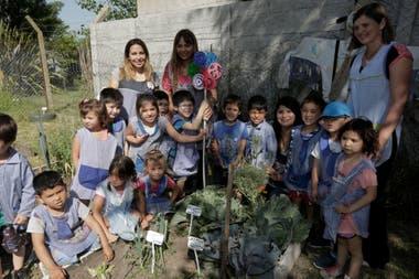 Las maestras jardineras reparten entre los chicos los alimentos que producen en la huerta.