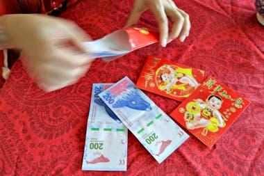 Este año, Liu preparó cuatro sobres rojos con dinero, que son para sus tres hijos y para la hija de unos amigos