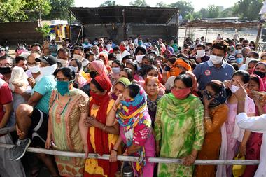 Los devotos hindúes esperan su turno para rendir homenaje a una estatua de la Diosa Kali en el Templo Antiguo Bhadrakali en Amritsar el 18 de mayo de 2020