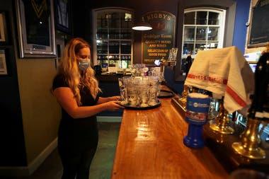 Una empleada lleva una bandeja de vasos vacíos, después de los últimos pedidos en el pub The Bridewell, en Liverpool, Gran Bretaña