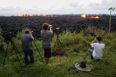 Fotógrafos toman imágenes del imponente camino de lava que atraviesa la isla