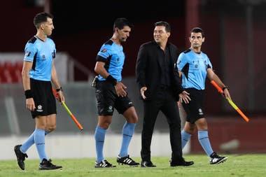 Gallardo y una sonrisa irónica al lado de los árbitros, después del partido.
