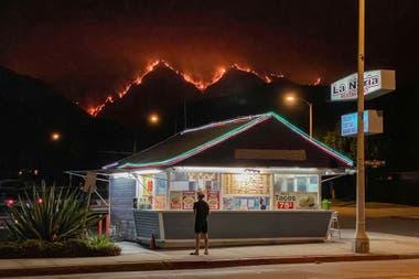 Un hombre se para frente a un restaurante de comida para llevar mientras el fuego devora las colinas cercanas a Monrovia, California