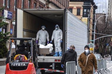 Los trabajadores médicos llevan un cuerpo a un camión refrigerado frente al Hospital de Brooklyn