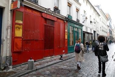 La gente pasa por un bar cerrado, como parte de las restricciones más estrictas debido al brote de la enfermedad del coronavirus (COVID-19) en París, Francia