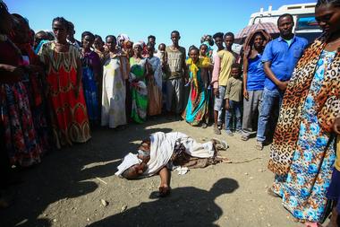Refugiados etíopes que huyeron de los combates en la región de Tigray rodean a una mujer que colapsó en el centro de recepción fronterizo Village 8 en el estado de Gedaref, en el este de Sudán, el 20 de noviembre de 2020