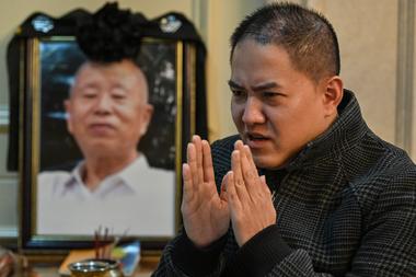 Esta foto tomada el 24 de noviembre de 2020 muestra a Liu Peien junto a un retrato de su padre, quien murió después de tener síntomas de Covid-19, en Wuhan, provincia central de Hubei en China