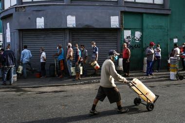 La gente forma fila para conseguir agua en las calles de Caracas; la pobreza y el trabajo informal son el mayor problema para cumplir la cuarentena en Venezuela