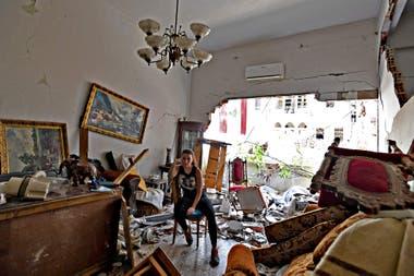 Una mujer sentada entre los escombros de su casa dañada en la capital libanesa, Beirut