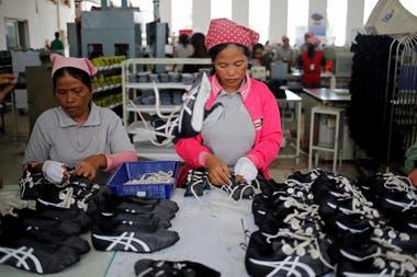 Mujeres trabajan en la línea de producción en Complete Honor Footwear Industrial