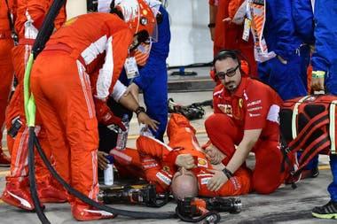 El mecánico Francesco Cigarini en el piso, después de ser arrollado por Kimi Räikkonen en el Gran Premio de Bahréin 2018; el italiano, de Ferrari, encargado del neumático trasero izquierdo, sufrió la fractura de la tibia y el peroné de la pierna izquierda