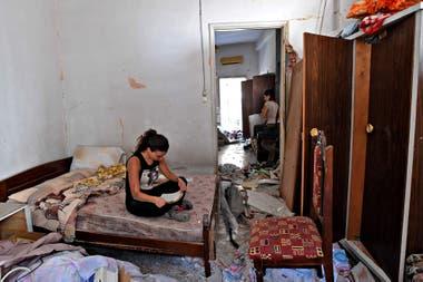 Una mujer limpia los escombros de su casa dañada en la capital libanesa, Beirut