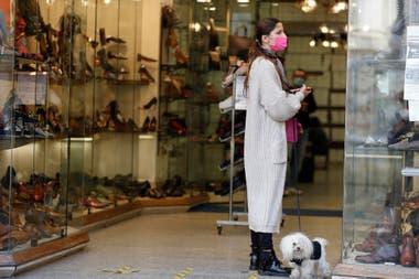 Una mujer con una máscara protectora sostiene a un perro mientras mira una zapatería cerca de la Fontana de Trevi, en Roma