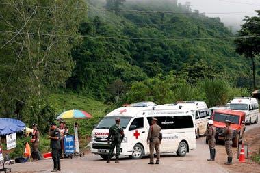 Policías y soldados tailandeses aseguran el área mientras las ambulancias manejan durante la operación de rescate