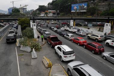 Los conductores hacen cola para reponer los tanques de sus automóviles en una estación de servicio, en Caracas, el 25 de mayo de 2020, en medio del brote de coronavirus
