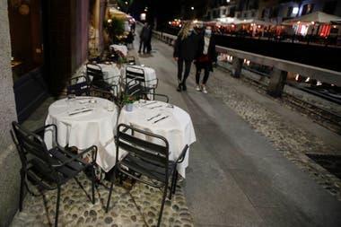 La gente pasa junto a las mesas vacías de un restaurante en el canal Naviglio Grande, uno de los lugares favoritos para la vida nocturna en Milán