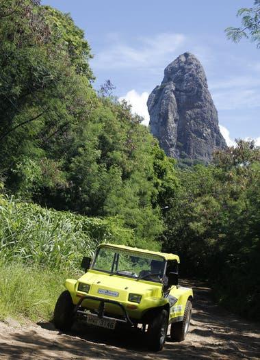 El buggy es el vehículo oficial de la isla y el Morro do Pico (detrás) es el punto más alto de Noronha
