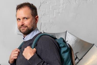 """Tomás Saraceno en su estudio de Berlín, con la mochila que permite transportar """"esculturas solares"""" y un paraguas diseñado para cocinar con energía solar"""