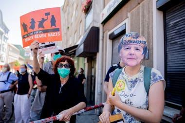 """Una mujer usa una máscara de la canciller de Alemania, Angela Merkel, con la inscripción """"Adiós democracia"""", durante una manifestación organizada por el grupo Querdenken 711, en contra de las medidas restrictivas impuestas por el gobierno para frenar el propagación del coronavirus"""