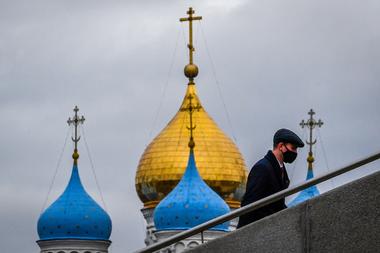 Un hombre que usa una mascarilla para protegerse contra el coronavirus sube las escaleras cerca del monasterio Novospassky de Moscú el 21 de octubre de 2020